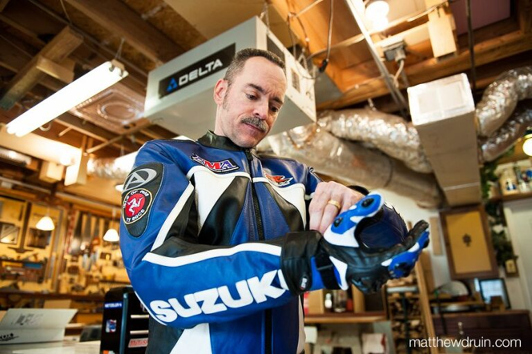 Portrait of guy putting on blue motorcycle suit in garage for American Motorcyclist Magazine