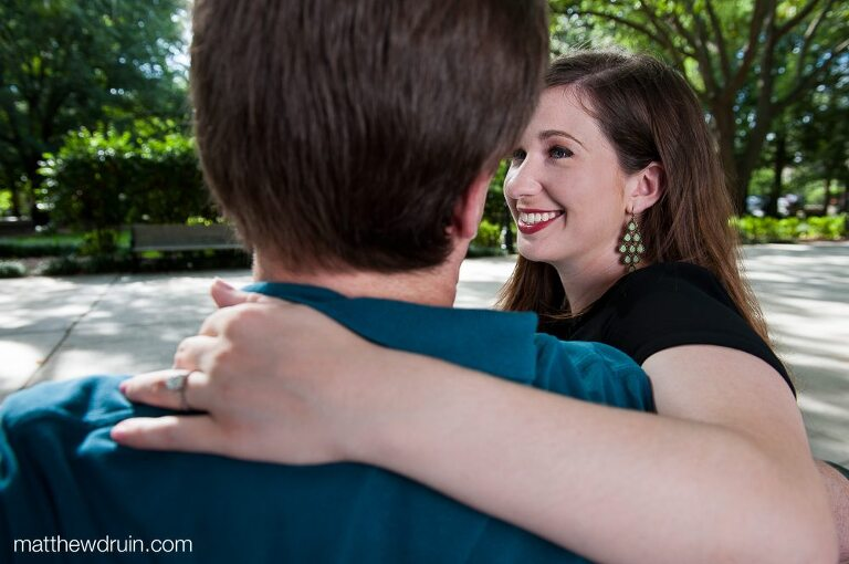 Engaged couple smiling at each other while sitting on park bench in Forsyth Park at savannah engagement session