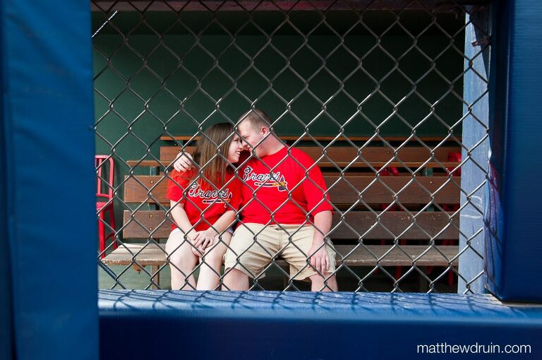 Engaged couple in dugout at Atlanta Braves Turner Field engagement session