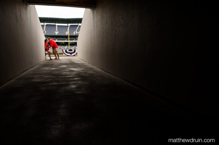 Engaged couple kissing at end of dark tunnel at Turner Field engagement session
