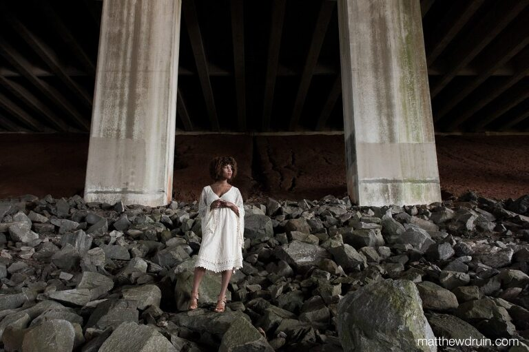 Editorial portraits Atlanta wedding harpist Maya Lately wearing white dress standing on large rock under highway bridge
