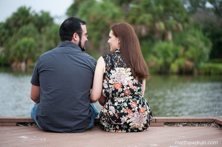 Engaged couple looking at each other while sitting on lake dock at New Orleans engagement