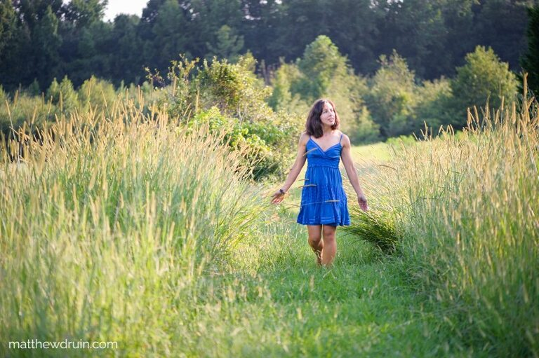 Girl walking in field with a blue dress in Atlanta at sunset