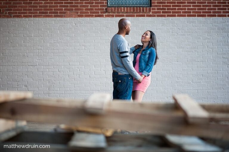 Engaged couple holding hands and standing in front of wood pallets at urban engagement session in Atlanta