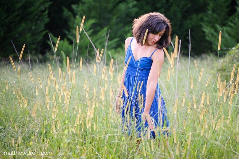 Girl standing in field with a blue dress in Atlanta at sunset