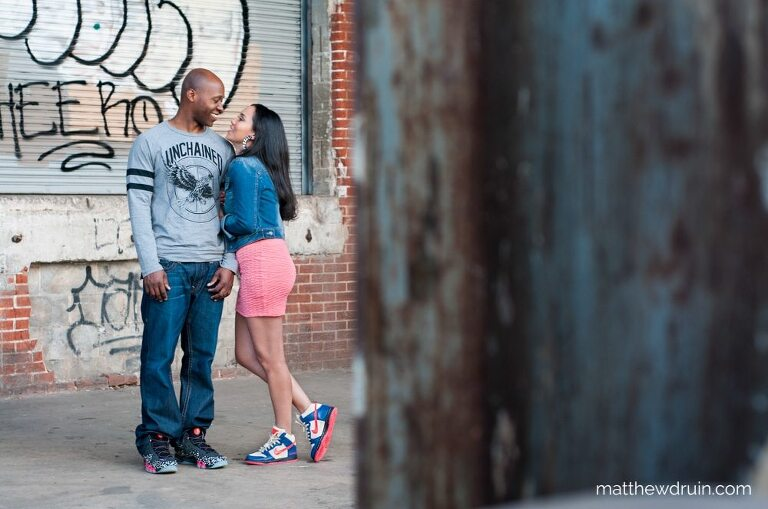 Engaged couple hugging in industrial area by loading dock at urban engagement session in Atlanta