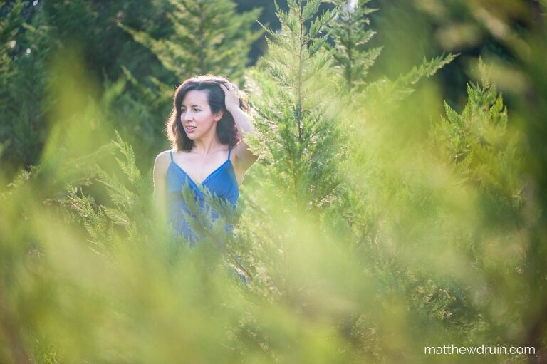 Girl standing in evergreen trees with a blue dress in Atlanta at sunset