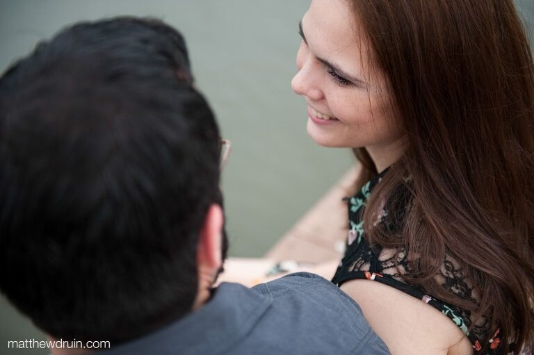 Engaged couple sitting on lake dock smiling at New Orleans engagement