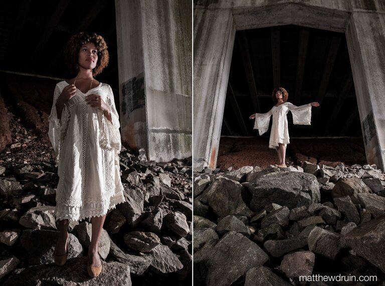 Editorial portrait of Atlanta wedding harpist Maya Lately under bridge wearing white dress standing on rocks