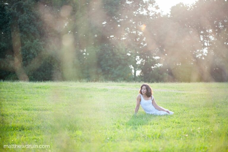 Girl sitting in field with a white dress in Atlanta at sunset