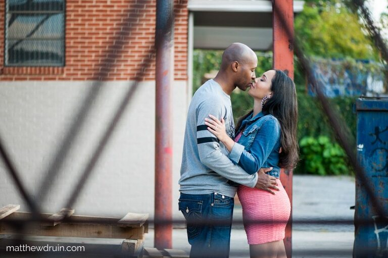 Engaged couple kissing in industrial area at urban engagement session in Atlanta