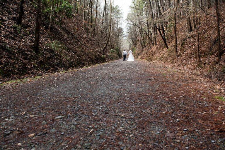 Wide shot of bride and groom walking down dirt road at Atlanta wedding in fall woods