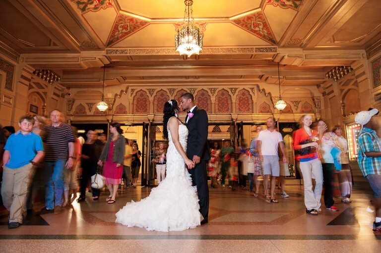 Atlanta bride and groom kissing with people walking past after Fox Theatre wedding getting your best wedding photos