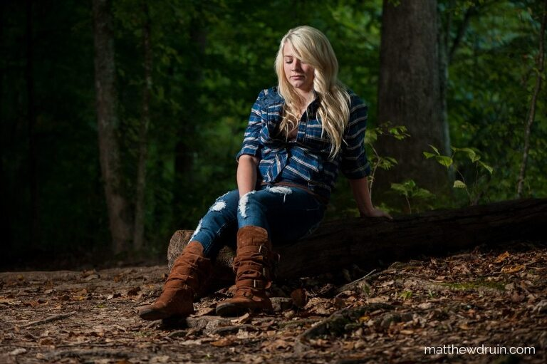 Blond girl wearing blue outfit sitting on log in woods by Chattahoochee River for Atlanta sunrise portraits