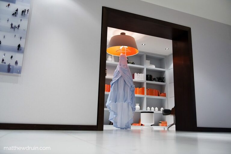 Brides blue dress hanging from modern orange lamp in Atlanta hotel