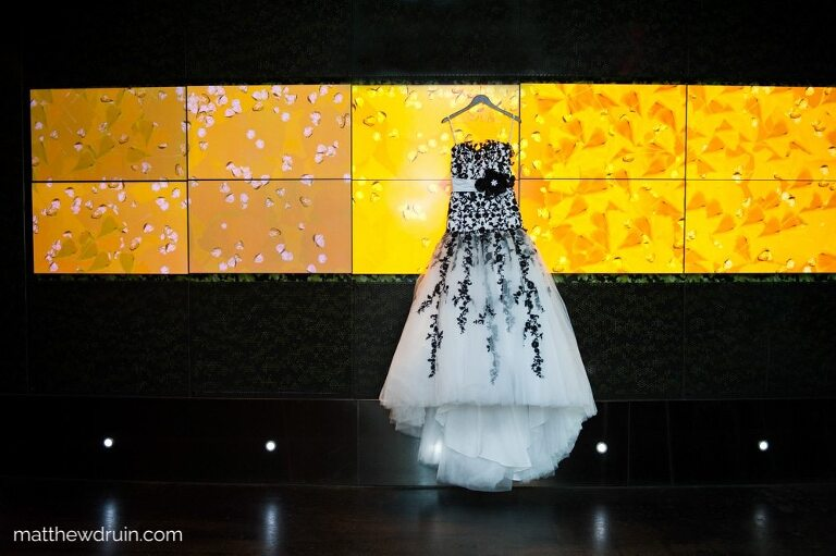 Brides white a black flower wedding dress hanging from yellow backlit artwork in W Hotel for Atlanta wedding