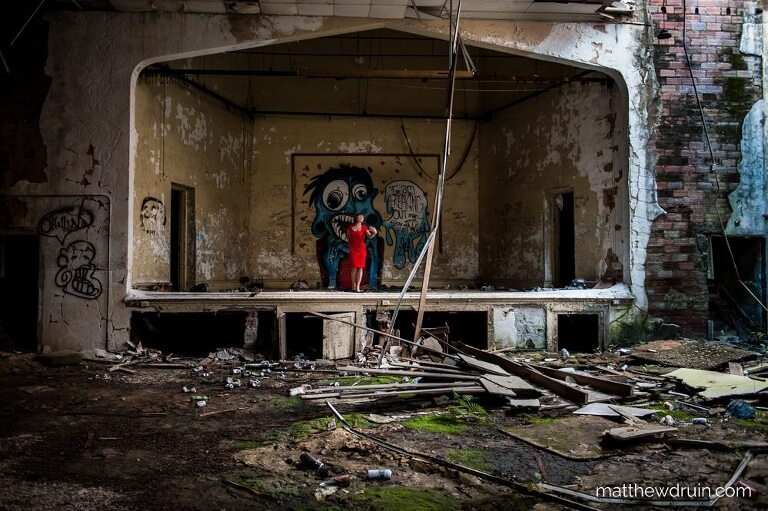 Wide shot of Red hair girl in red dress standing on theatre stage in abandoned Atlanta school