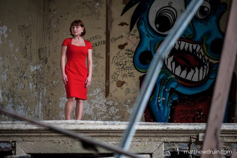 Red hair girl in red dress standing on theatre stage with blue graffiti in abandoned Atlanta school