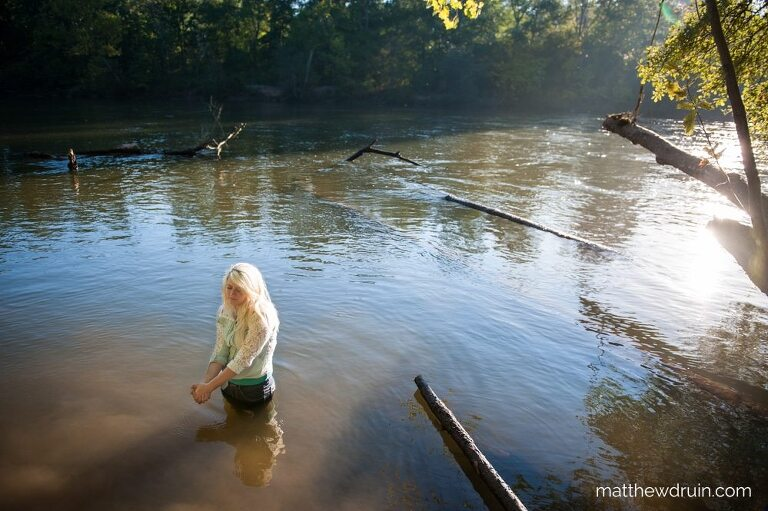 Girl with blond hair and tight white shirt standing in Chattahoochee River for Atlanta sunrise portraits