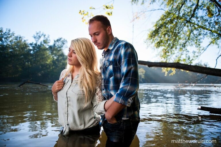 Engaged couple holding each other standing in Chattahoochee River for Atlanta sunrise portraits