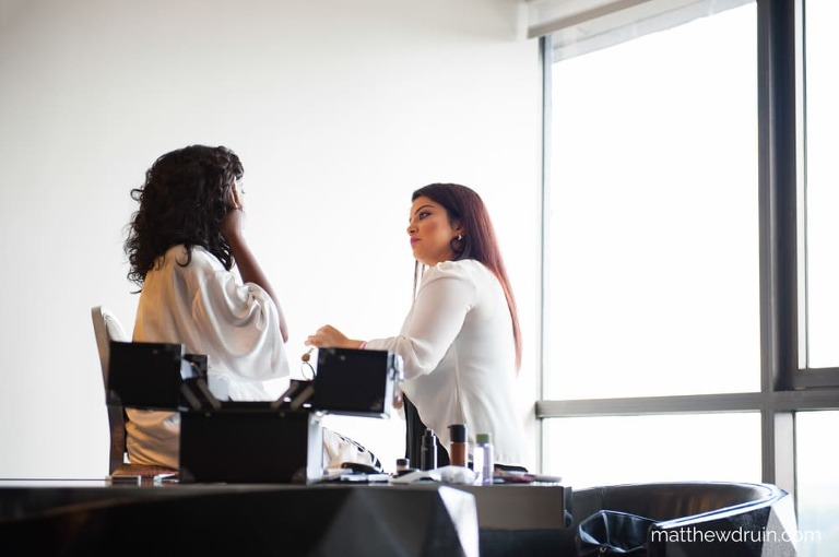 Makeup artist looking at brides face with giant glass window and blown out lighting getting ready for W Hotel Atlanta wedding