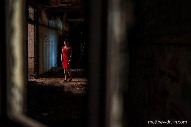 Red hair girl in red dress standing in creepy dark hallway with yellow sunlight shinning through in abandoned Atlanta school