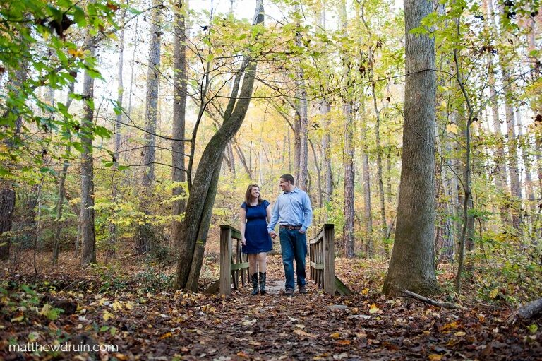 Engaged couple wearing walking across bridge in green woods for fall engagement