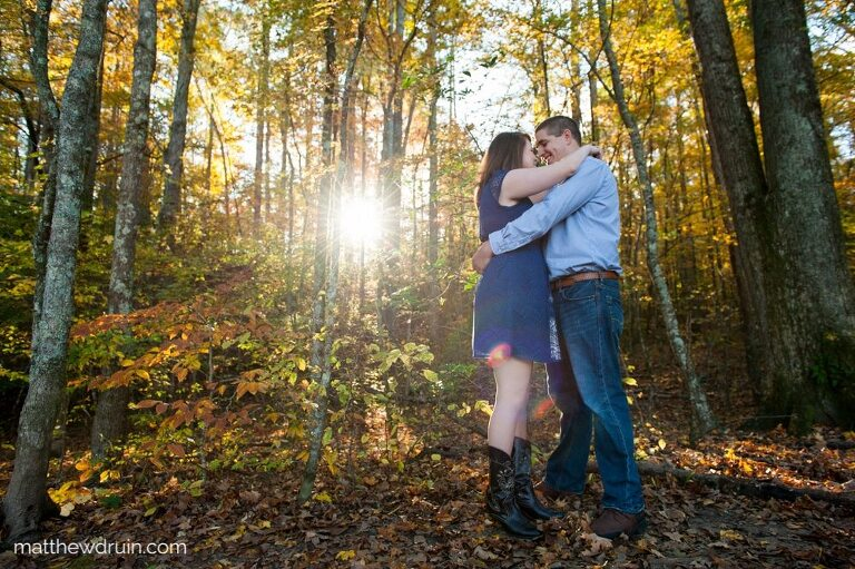 Engaged couple wearing blue in green woods with yellow sunset kissing for Atlanta fall engagement