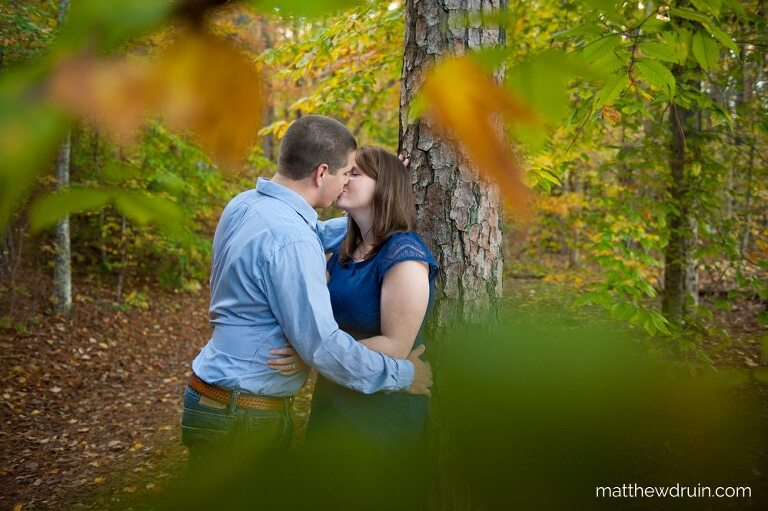 Couple kissing against tree for fall engagement
