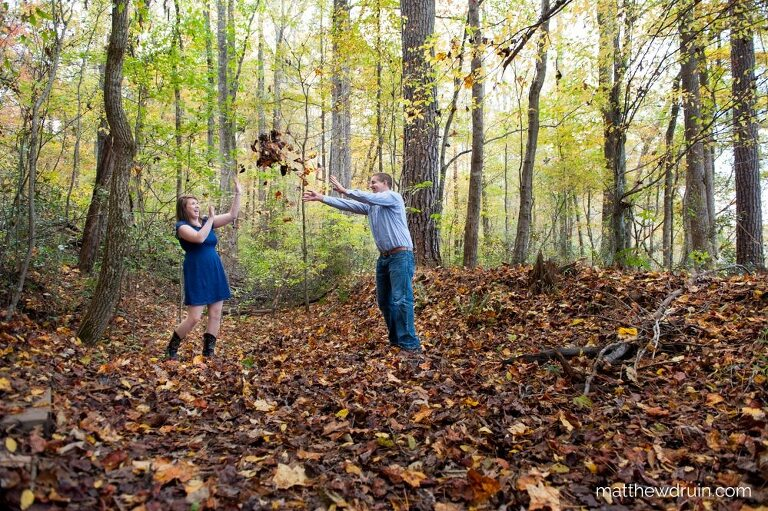 Couple throwing leaves for fall engagement