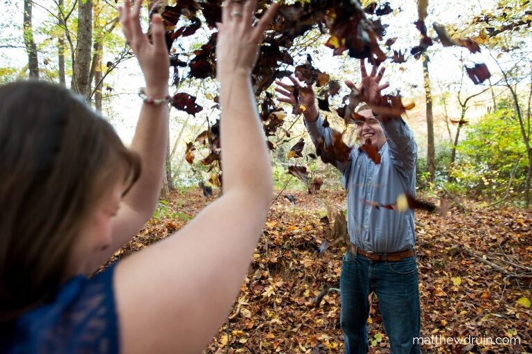 Couple throwing leaves at each other for fall engagement