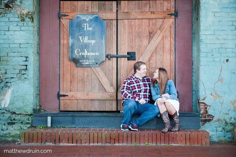 Engaged couple sitting on stairs of the Village Craftsman during Savannah engagement session