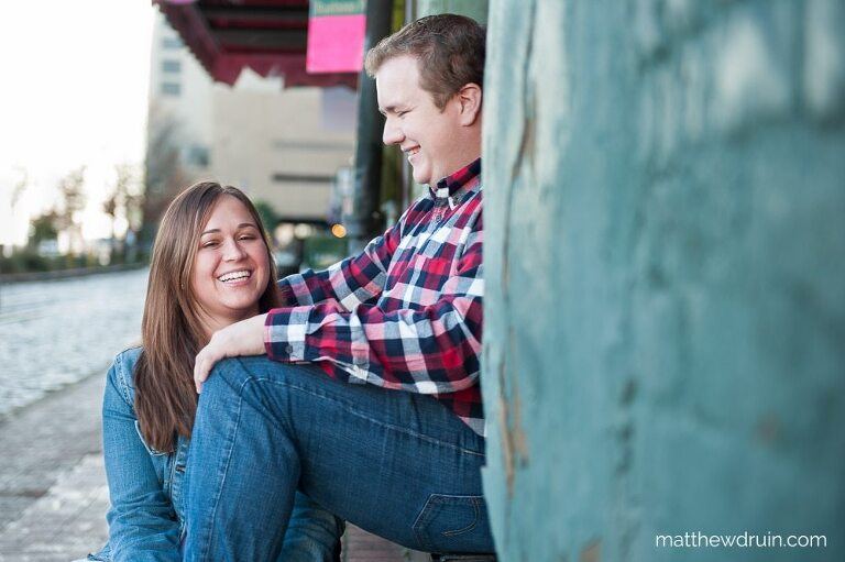 Engaged couple laughing sitting on blue green wall during Savannah engagement session