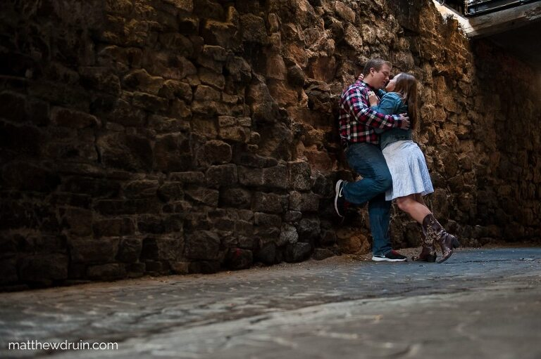 Engaged couple kissing under street light under bridge during Savannah engagement session