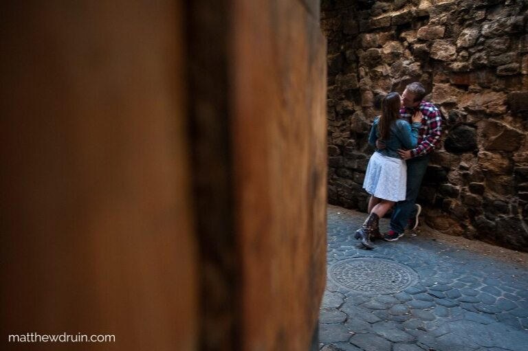 Engaged couple kissing under street light leaning against wall during Savannah engagement session