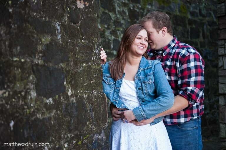 Engaged couple hugging against wall during Savannah engagement session