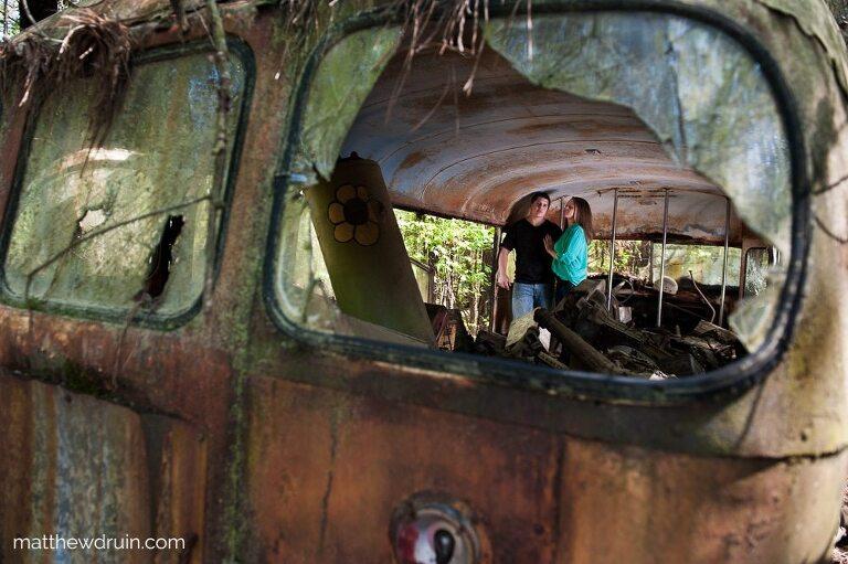 Engaged couple hugging inside old abandoned yellow bus shot through broken window