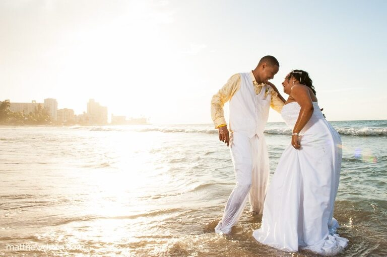 Bride and groom in wedding dress in the ocean at sunset during Puerto Rico wedding