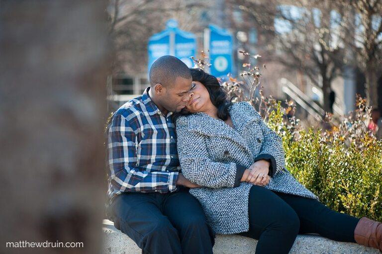 Engaged couple sitting on brick wall outside Georgia Aquarium in winter coats during Georgia Aquarium engagement