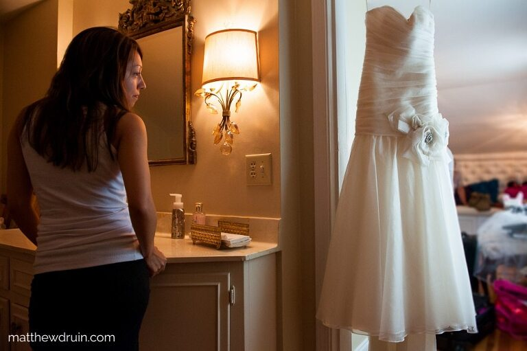 Bride in bathroom looking at her wedding dress hanging from door at Atlanta wedding