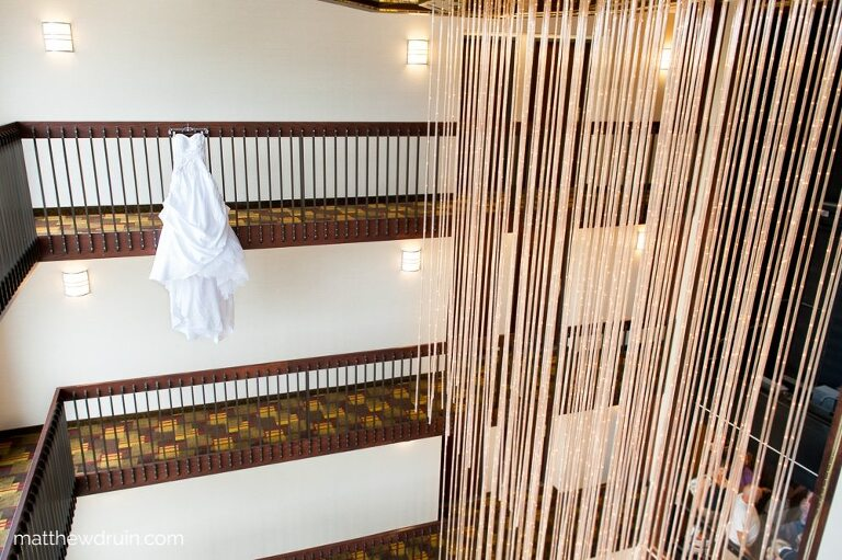 Brides white wedding dress hanging from 12th floor hotel balcony with tons of yellow rope lights hanging from ceiling for Atlanta wedding