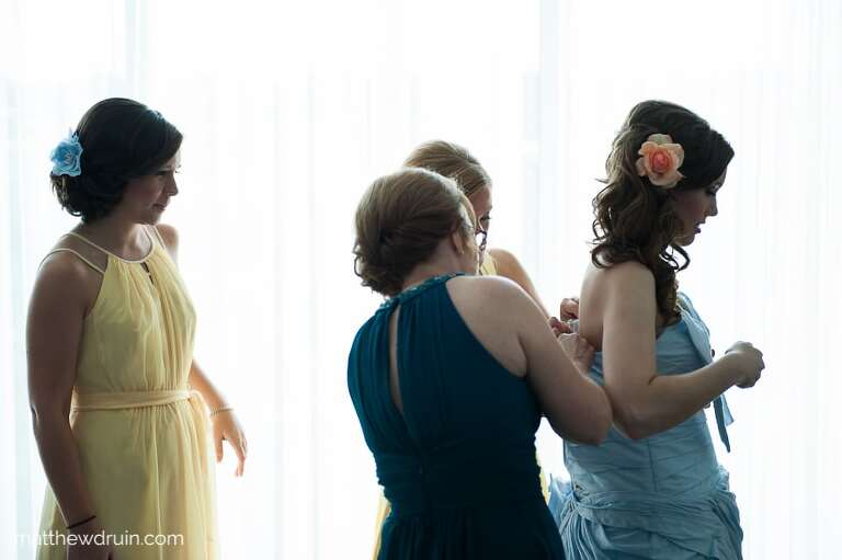 Bridesmaids helping bride put on her blue wedding dress in front of light-filled large window for Atlanta wedding