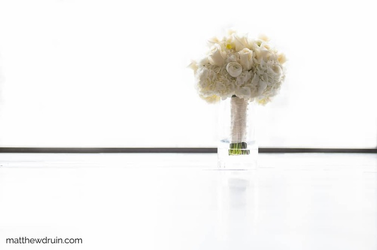 Brides white flower bouquet in front of white window for Atlanta wedding