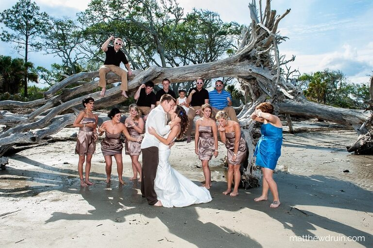 Bride and groom kissing with wedding party making faces on beach during Jekyll Island wedding