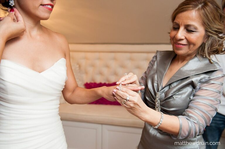 Mom putting diamond bracelet on bride while getting ready for Atlanta wedding