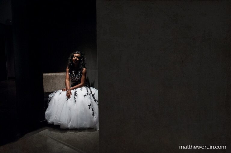 Bride with white and black wedding dress sitting in spotlight in darkened room at Atlanta W Hotel