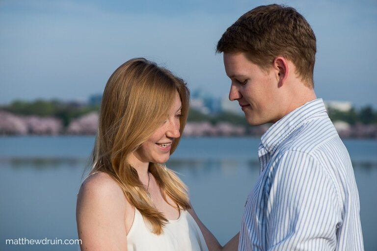 Engaged couple standing by lake at sunset with cherry blossoms in background at Washington DC engagement session