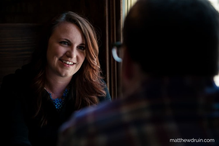 Girl smiling at guy sitting at table with window light in Terminal Brewhouse during Chattanooga engagement session