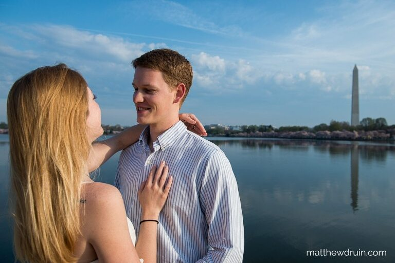 Engaged couple standing by lake at sunset with Washington monument in background at Washington DC engagement session