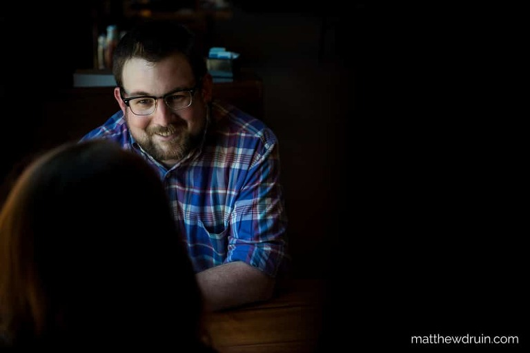 Guy smiling at girl sitting at table in Terminal Brewhouse during Chattanooga engagement session